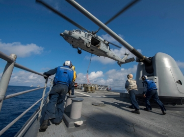 An MH-60S Sea Hawk helicopter lowers supplies to the deck of the guided-missile cruiser USS San Jacinto