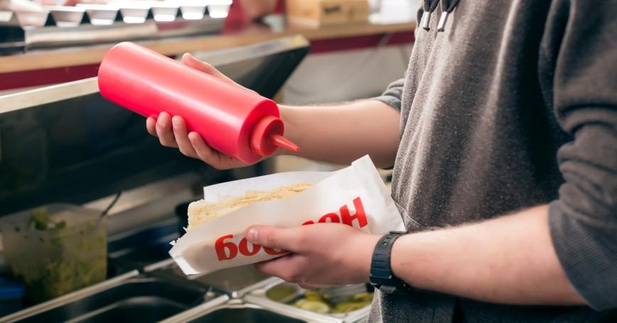 man putting ketchup on a hot dog at a snack bar