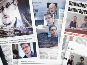 A collection newspapers with pictures and publications of Edward Snowden