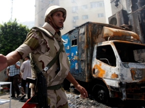 A soldier stands outside the burnt Rabaa Adawiya mosque