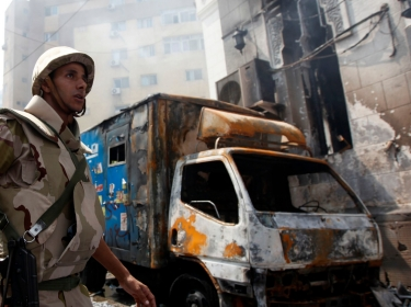 A soldier stands outside the burnt Rabaa Adawiya mosque, the morning after the clearing of a protest camp around the mosque, in Cairo August 15, 2013.