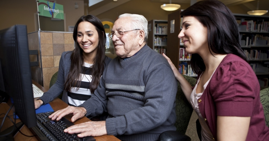 women helping a senior man in a library