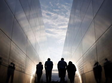 People walk through the 9-11 Empty Sky memorial across from New York's One World Trade Center at Liberty State Park in Jersey City, NJ