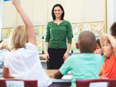 teacher wearing green sweater talking to elementary students