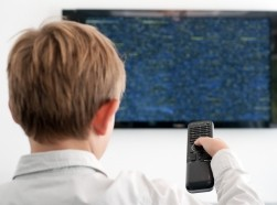A boy points a remote control at a television