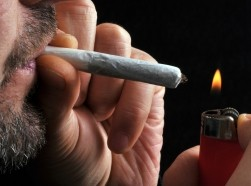A man lights a marijuana cigarette.
