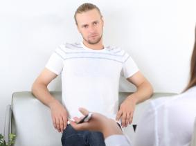male patient wearing white shirt talking to psychiatrist