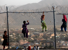 Afghan children climb onto a fence while playing as they sell tea in Kabul
