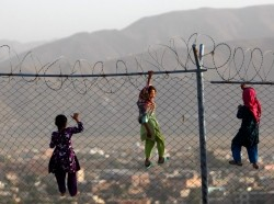 Children climb a fence in Kabul, Afghanistan, September 4, 2013