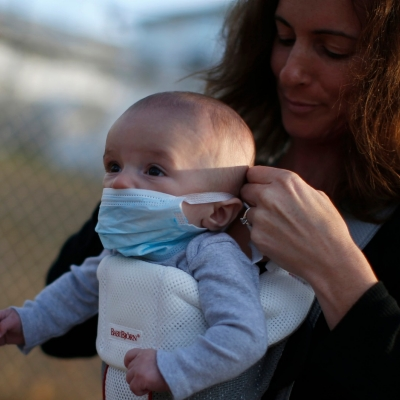 A mother on Staten Island straps a protective mask onto her baby after Hurricane Sandy