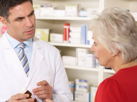 a pharmacist speaking with a woman in a pharmacy