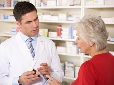 American pharmacist with senior woman in pharmacy