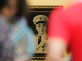 People pay their respects in front of a portrait of General Vo Nguyen Giap at his house in Hanoi October 6, 2013