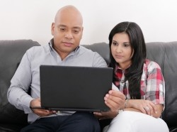 young couple looking at their finances on a laptop on a couch