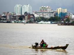 Men travel in a boat across the Yangon river