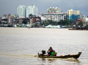 Men travel in a boat across the Yangon river