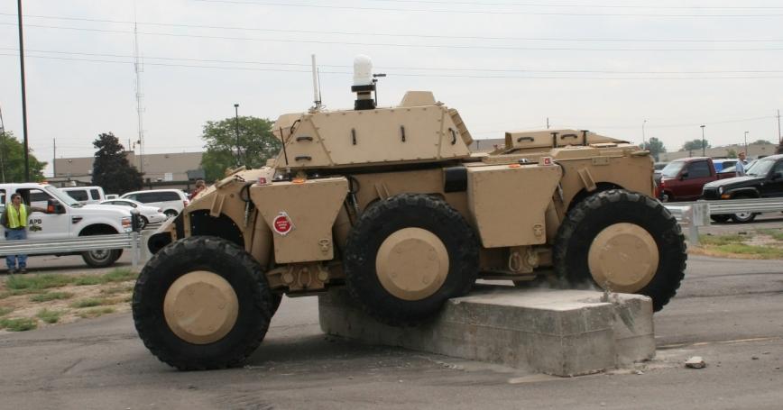 A autonomous vehicle maneuvers over concrete blocks during a demonstration.