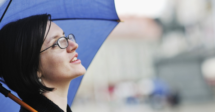 woman carrying umbrella looking up at sky