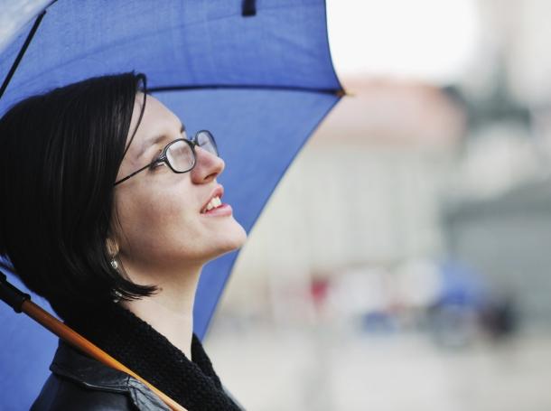 woman carrying umbrella looking up at sky