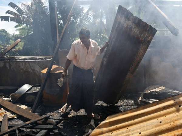 A man clears debris from a mosque that was burnt down in Myanmar's Rakhine state