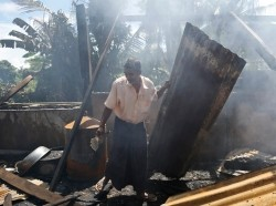 A man clears debris from the mosque that was burnt down in Myanmar's Rakhine state