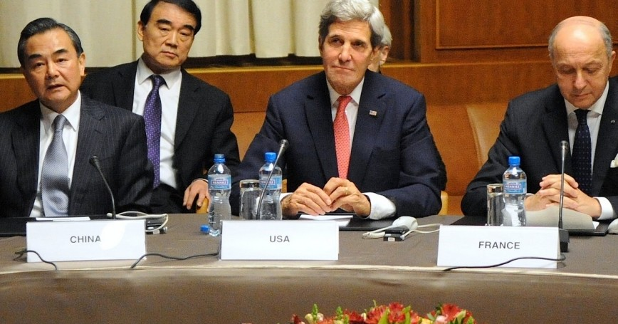 U.S. Secretary of State John Kerry sits between Chinese Foreign Minister Wang Yi and French Foreign Minister Laurent Fabius at the United Nations Headquarters after the P5+1 member nations concluded a nuclear deal with Iran in Geneva, Switzerland, on November 24, 2013