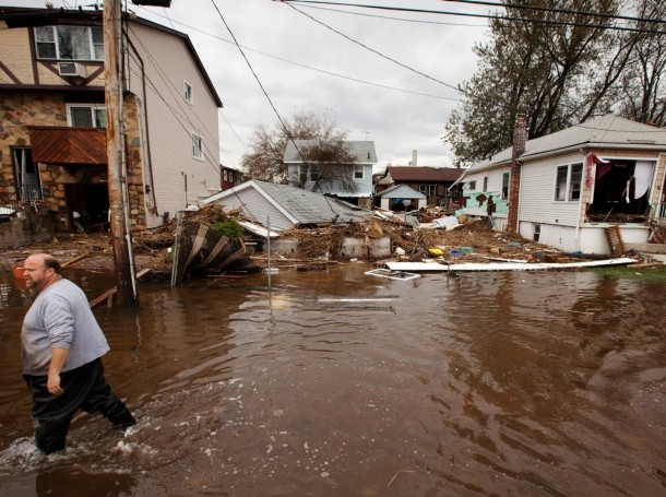 men walk through flooding left by the storm surge of Superstorm Sandy in the New Dorp Beach neighborhood of  Staten Island
