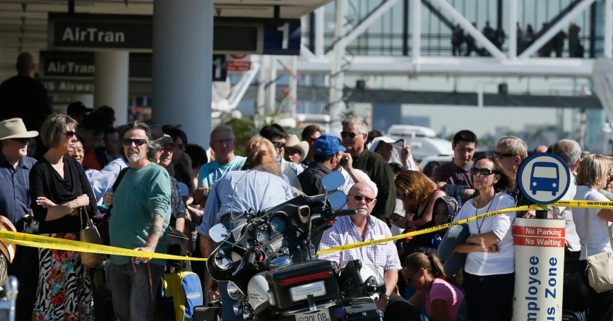 Delayed passengers stand behind a police cordon after a shooting incident at Los Angeles airport