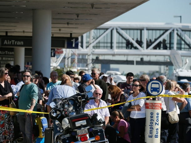Delayed passengers stand behind a police cordon after a shooting incident at Los Angeles airport (LAX)