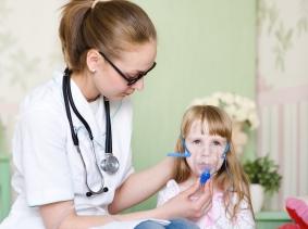 Doctor holding inhaler mask on girl