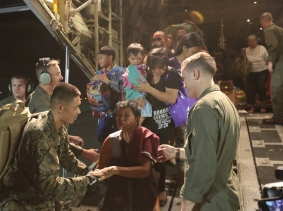 U.S. Marines help displaced Philippine nationals from the back of a KC-130J Super Hercules at Vilamor Air Base, Manila, Republic of the Philippines