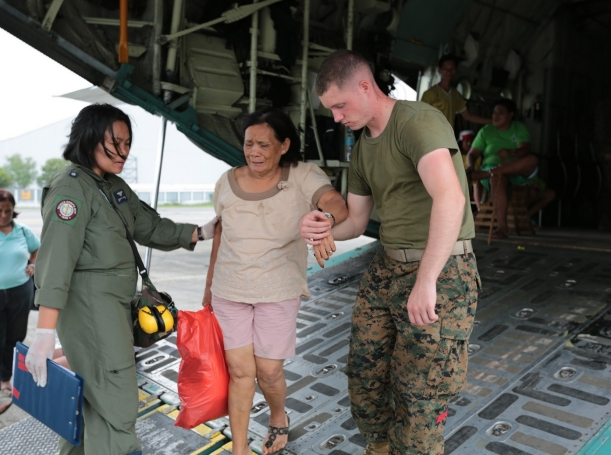 A U.S. Marine and a Philippine airman assist an injured Filipino woman off a KC-130J Super Hercules at Vilamore Air Base, Manila, Republic of the Philippines