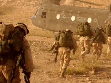 Soldiers quickly walk to the ramp of the CH-47 Chinook cargo helicopter that will return them to Kandahar Army Air Field.