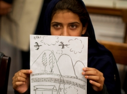 Pakistani girl holds up a picture she drew depicting the U.S. drone strike on her village which killed her grandmother