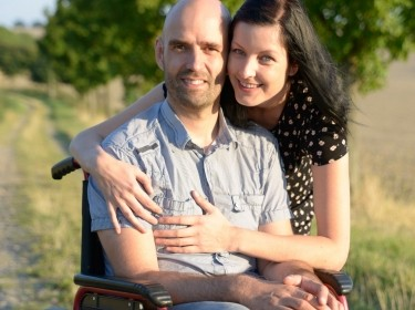 a man in a wheelchair with his wife and caregiver