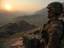 A soldier watches the sun rise after spending the night on a night observation post