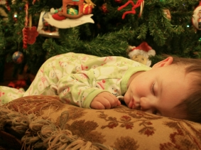 child sleeping near a Christmas tree