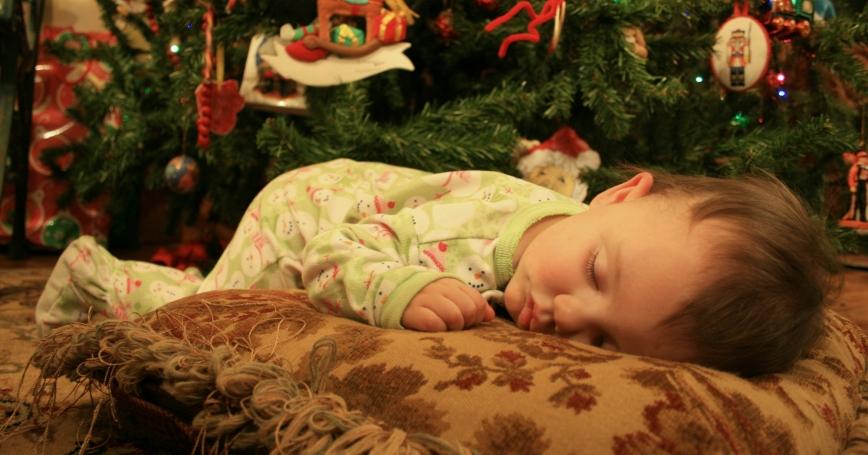 child sleeping near a Christmas tree