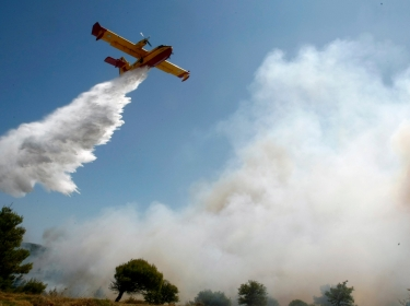 A Hellenic Air Force Canadair CL-415 drops water over a forest fire northeast of Athens in August 2009