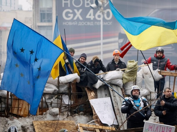 Ukrainian pro-EU demonstrators wave EU and Ukraine flags at a barricade in Independence Square in Kiev, December 18, 2013