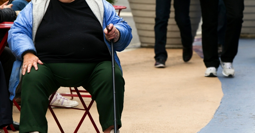 An overweight person sits on a chair in Times Square