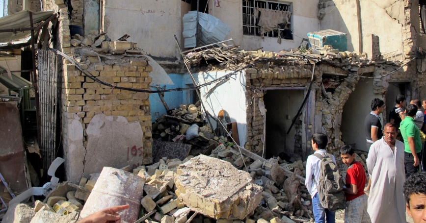 Two boys look at the site of a car bomb attack in Baghdad
