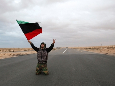 An anti-Gaddafi rebel prays and chants along a road during clashes with pro-Qaddafi forces March 2011
