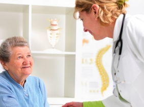 older woman shaking hands with a doctor