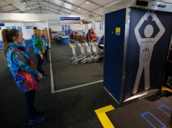Volunteers wait to enter through a security check point in the Costal Athletes Village as preparations continue for the Sochi 2014 Winter Olympics