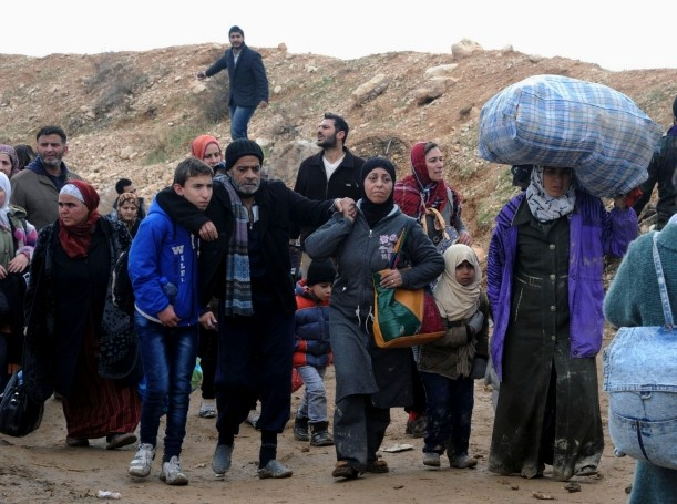 Syrian residents flee their homes following clashes between opposition fighters and forces loyal to President Bashar al-Assad