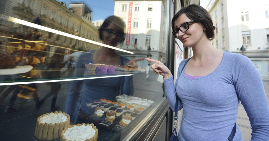 woman looking into a bakery window