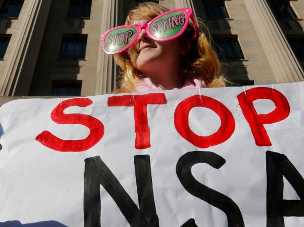 Member of the protest group, Code Pink, protests against U.S. President Barack Obama and the NSA before his arrival at the Department of Justice in Washington, January 17, 2014