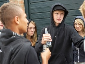 teens standing around outside drinking