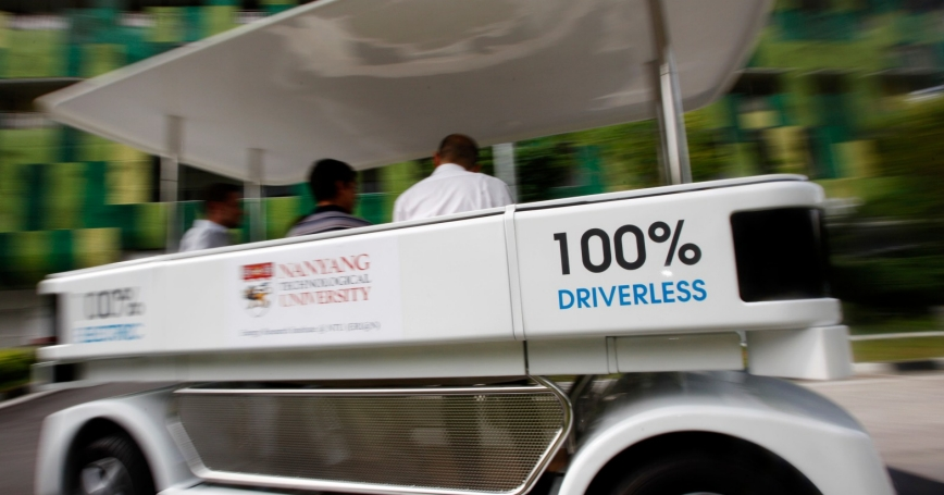 People ride on a driverless electric vehicle at the Nanyang Technological University in Singapore